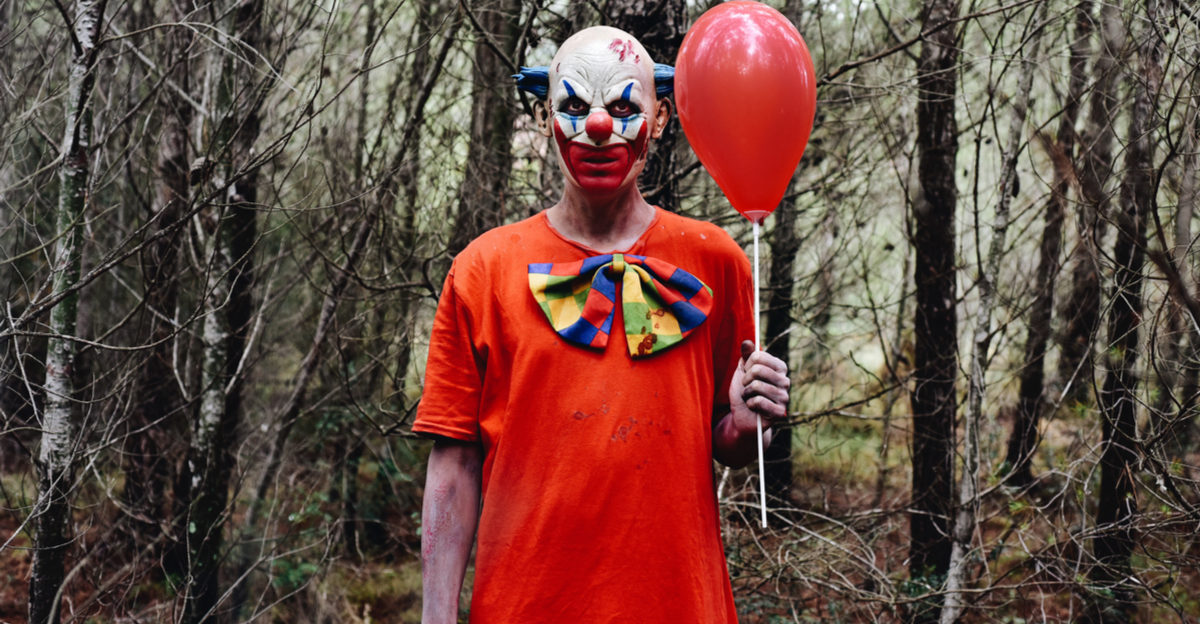 Shutterstock/ a scary evil clown wearing a dirty costume, holding a red balloon in his hand, in the woods  (Shutterstock/nito)