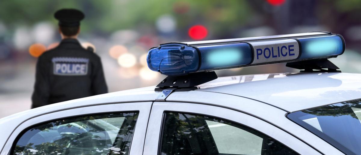 Shutterstock/ Police officer emergency service car driving street with siren light blinking