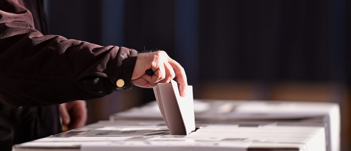 Hand of a person casting a vote into the ballot box during elections roibu (Shutterstock)