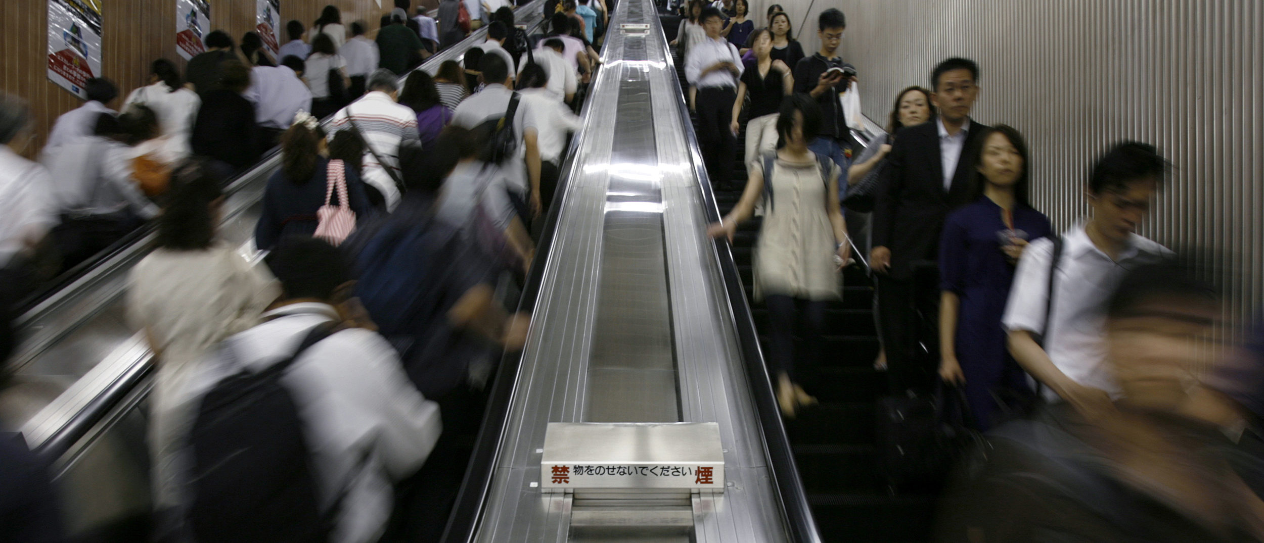 Commuters ride escalators at a subway station in Tokyo August 12, 2009.   REUTERS/Stringer (JAPAN BUSINESS EMPLOYMENT) - RTR27B7S