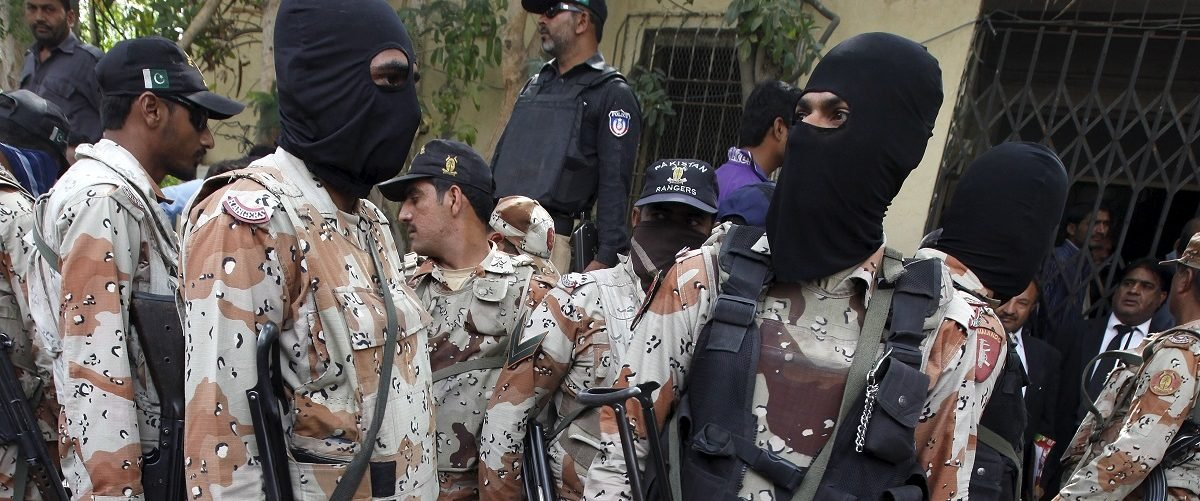 Pakistan Rangers stand guard near some men, who were detained during a raid on the Muttahida Qaumi Movement (MQM) political party headquarters, to present them before an anti-terrorism court in Karachi, Pakistan, March 13, 2015. Pakistan's main opposition party on Thursday accused the powerful army of trying to usurp the powers of a provincial government, intensifying a showdown between the military and politicians in Pakistan's biggest and richest city. Picture taken March 13, 2015. REUTERS/Akhtar Soomro.