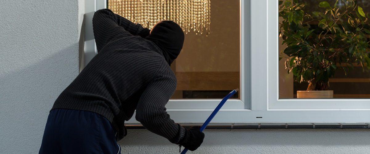 Masked burglar attempts to break into house. Photographee.eu/Shutterstock.