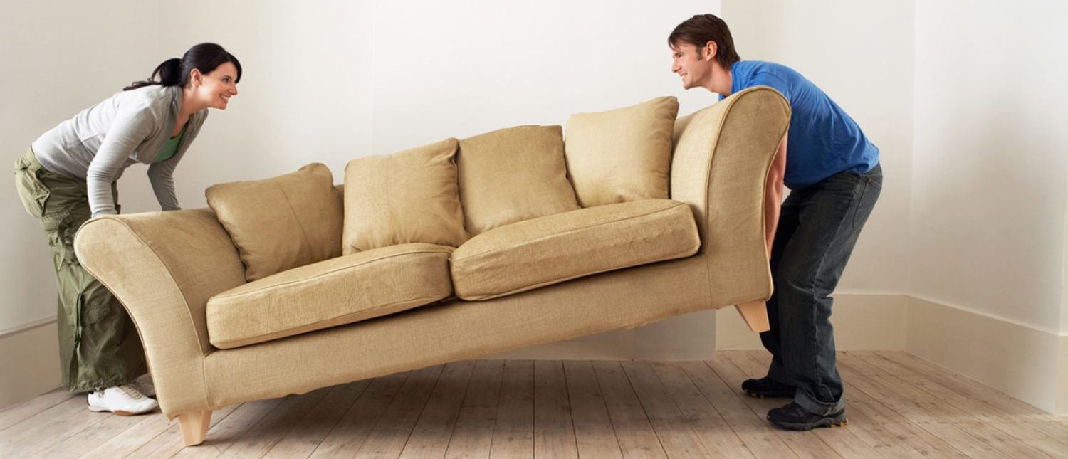 Side view of happy young couple placing sofa in living room of new home. [Shutterstock - sirtravelalot]