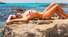 A girl lays on a rock wearing a red, white and blue bikini with the ocean in the background. (photo: Shutterstock)