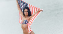 Beautiful brunette poses on beach with American flag. (photo: Shutterstock)