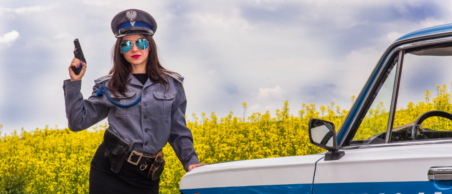 Policewoman stands by police car (Shutterstock/Damian Pankowiec)