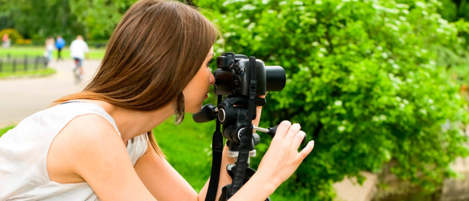 A woman snapping a photo with her camera and tripod. [Shutterstock - krechet]