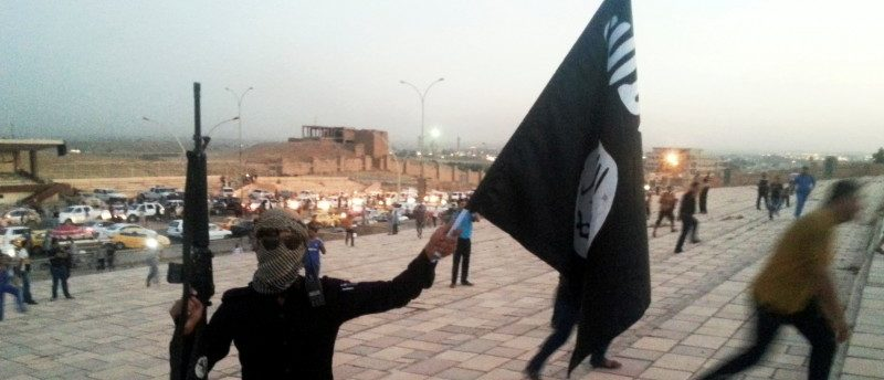 FILE PHOTO: A fighter of the Islamic State of Iraq and the Levant (ISIL) holds an ISIL flag and a weapon on a street in the city of Mosul, Iraq, June 23, 2014. REUTERS/Stringer/File Photo