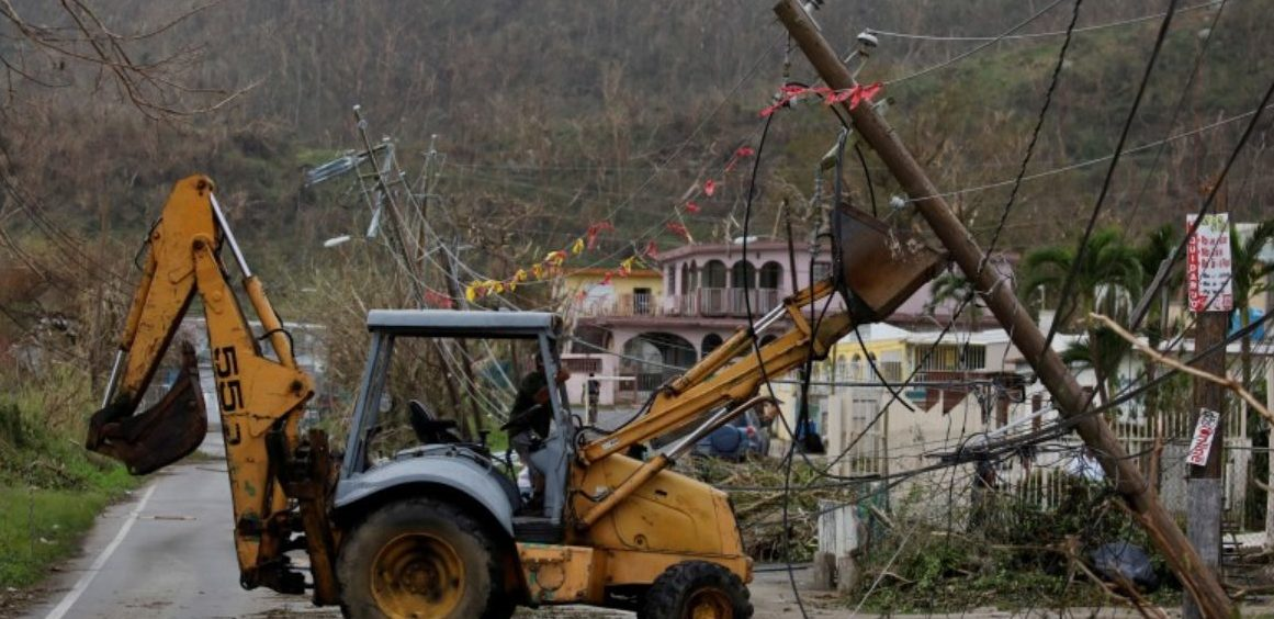 FILE PHOTO: A worker uses a backhoe loader to remove damaged electrical installations from a street after the area was hit by Hurricane Maria in Yabucoa, Puerto Rico September 22, 2017. REUTERS/Carlos Garcia Rawlins/File PHoto
