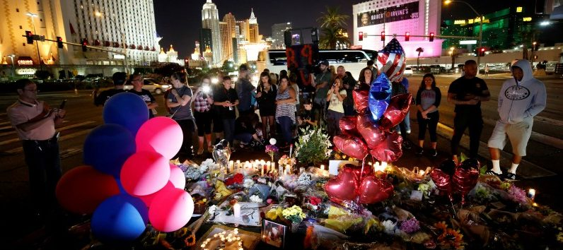 People gather at a makeshift memorial in the middle of Las Vegas Boulevard following the mass shooting in Las Vegas, Nevada, U.S., October 4, 2017. REUTERS/Chris Wattie