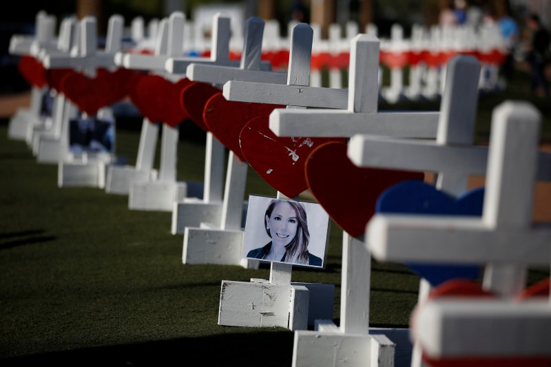 A photograph hangs from one of the 58 white crosses set up for the victims of the Route 91 music festival mass shooting in Las Vegas, Nevada, U.S., October 5, 2017. REUTERS/Chris Wattie