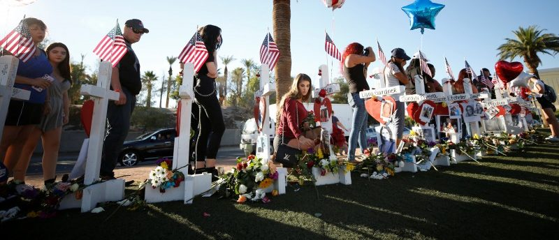 A woman places a flower in front of one of many white crosses set up for the victims of the Route 91 Harvest music festival mass shooting in Las Vegas, Nevada, U.S., October 6, 2017. REUTERS/Chris Wattie