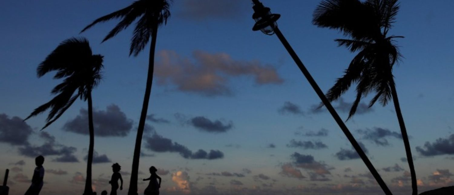 People are seen in silhouette walking on a beach affected by Hurricane Maria in San Juan, Puerto Rico, October 13, 2017. REUTERS/Shannon Stapleton