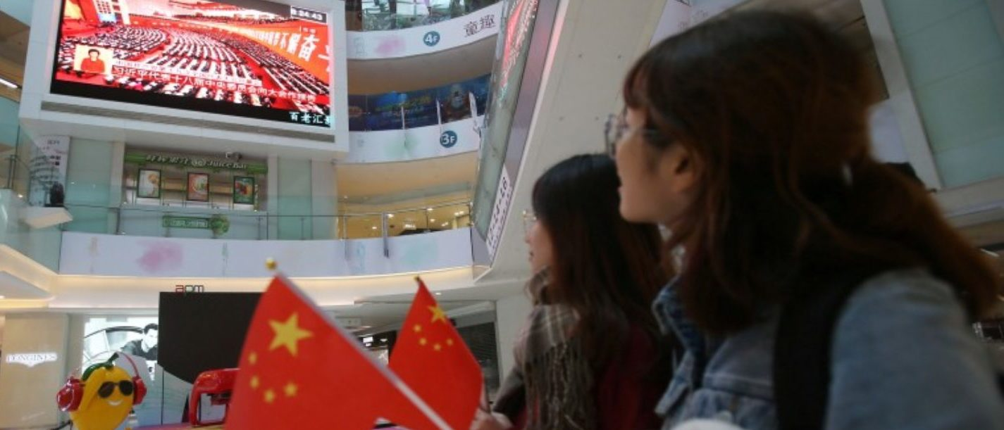 People watch a broadcast of Chinese President Xi Jinping delivering his speech during the opening of the 19th National Congress of the Communist Party of China, at a shopping mall in Beijing, China October 18, 2017. REUTERS/Stringer