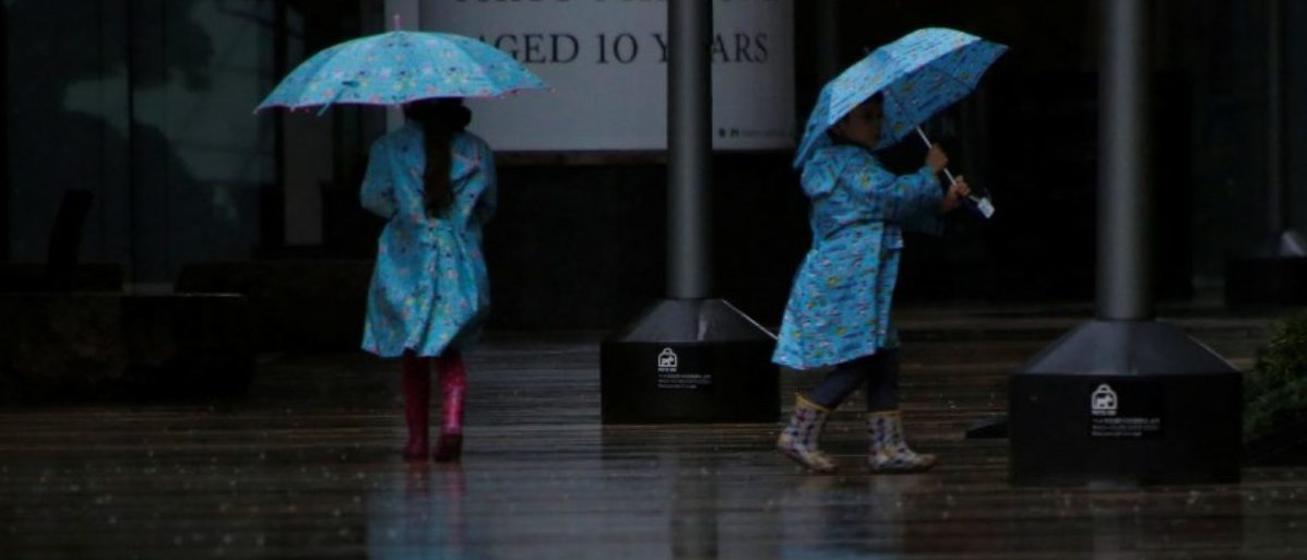 Children wearing rain suits walk in a heavy rain as Typhoon Lan approaches Japan's mainland, in Tokyo, Japan, October 22, 2017. REUTERS/Issei Kato