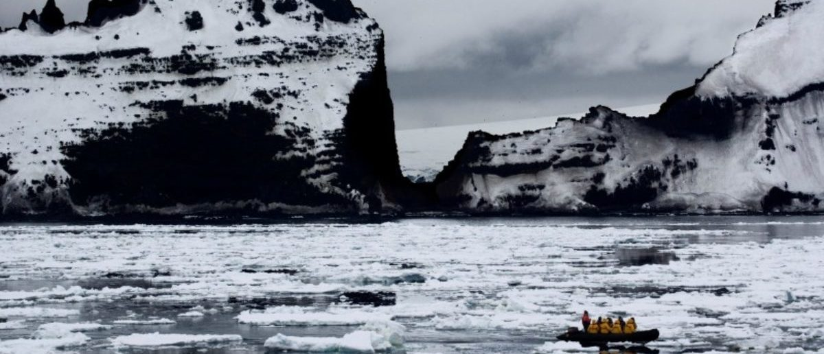 A supplied image shows a boat passing a rocky cliff in Antarctica