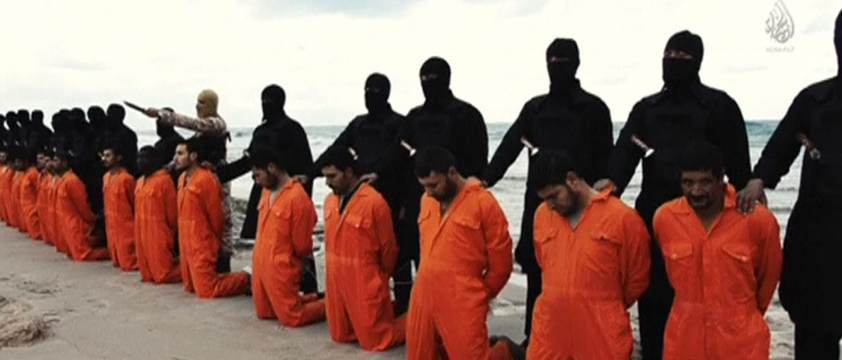 Men in orange jumpsuits purported to be Egyptian Christians held captive by the Islamic State (IS) kneel in front of armed men along a beach said to be near Tripoli, in this still image from an undated video made available on social media on February 15, 2015. Islamic State released the video on Sunday purporting to show the beheading of 21 Egyptian Christians kidnapped in Libya. In the video, militants in black marched the captives to a beach that the group said was near Tripoli. They were forced down onto their knees, then beheaded. Egypt's state news agency MENA quoted the spokesman for the Coptic Church as confirming that 21 Egyptian Christians believed to be held by Islamic State were dead. REUTERS/Social media via Reuters TV