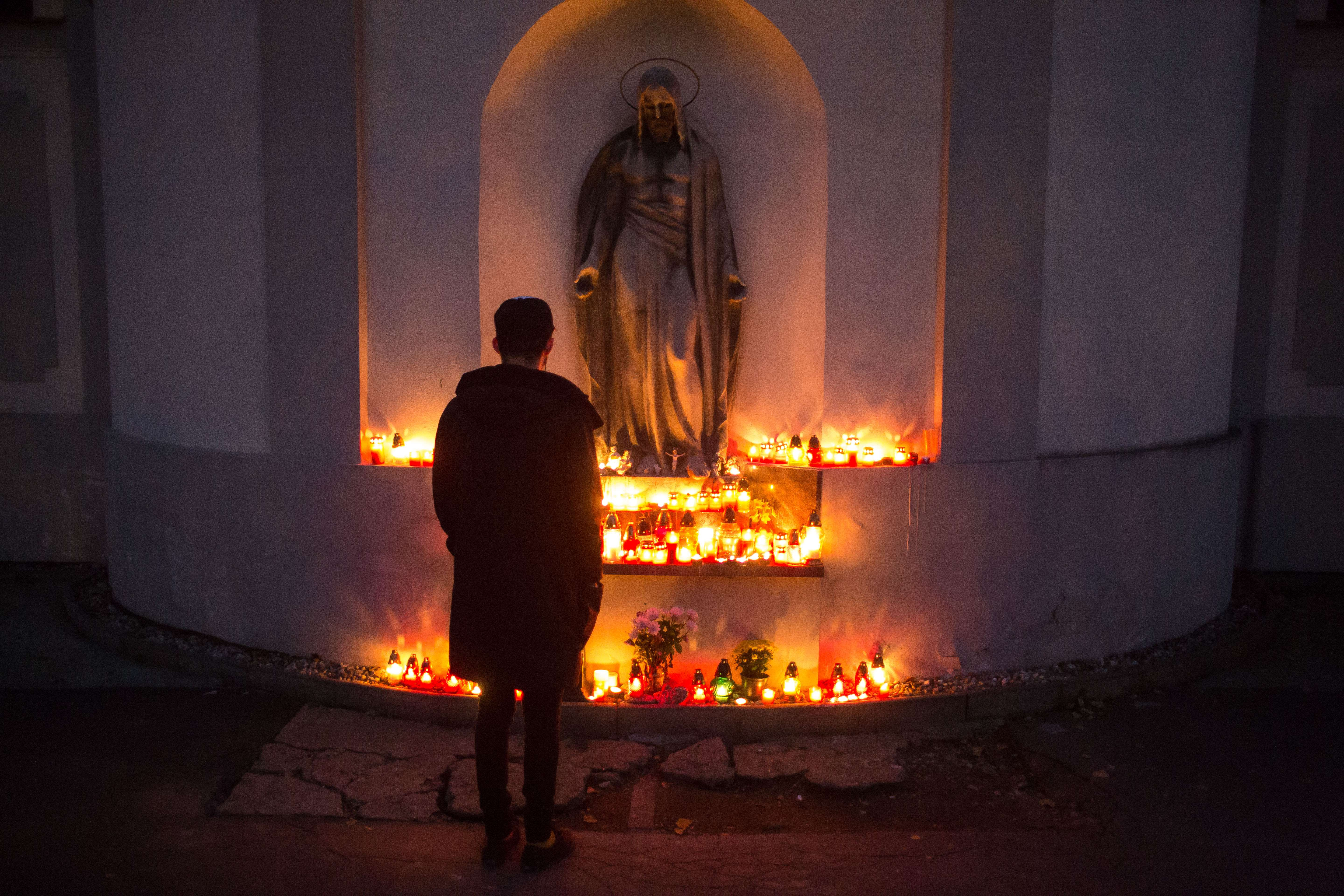 A man looks at candles placed at the Slavicie udolie cemetery in Bratislava on All Saints' Day, November 1, 2015. (VLADIMIR SIMICEK/AFP/Getty Images)