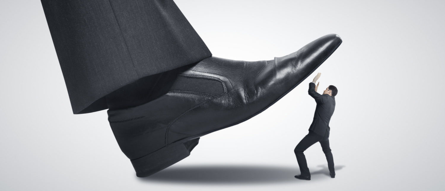 Proverbial image of a tech giant stepping on a small business owner. [Shutterstock - Peshkova]