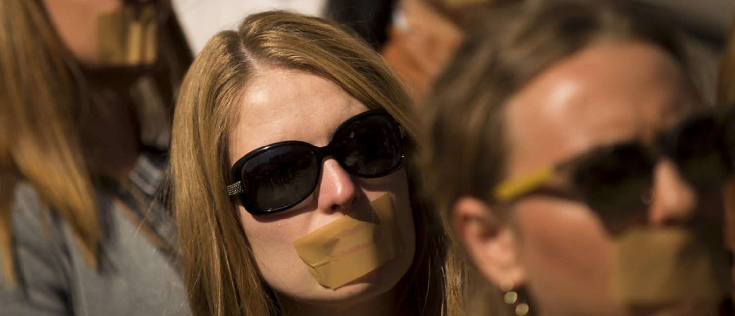 Journalists protest against censorship with taped mouths. [Shutterstock - Veselin Borishev]