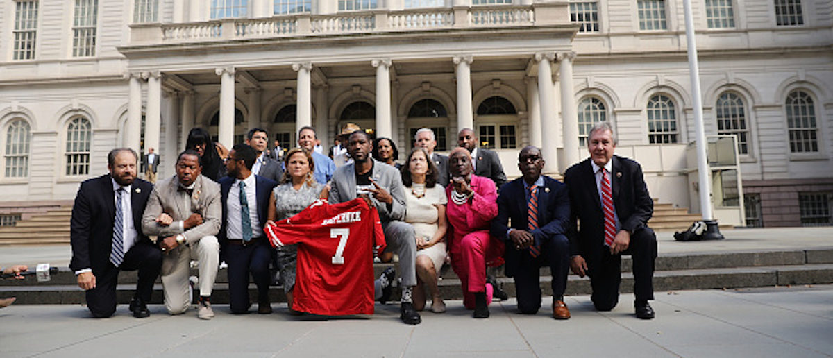 NEW YORK, NY - SEPTEMBER 27: City Council Members, including Jumaane Williams (center right) and Melissa Mark-Viverto (center left) 'take a knee' on the steps of City Hall in reaction to President Donald Trump's condemnation of NFL players who do the same on September 27, 2017 in New York City. The Council members spoke of having solidarity with athletes and coaches around the country who have also kneeled in protest of racial injustice, especially in policing. Council member Jumaane Williams held a football jersey with quarterback Colin Kaepernick's name on it. (Photo by Spencer Platt/Getty Images)