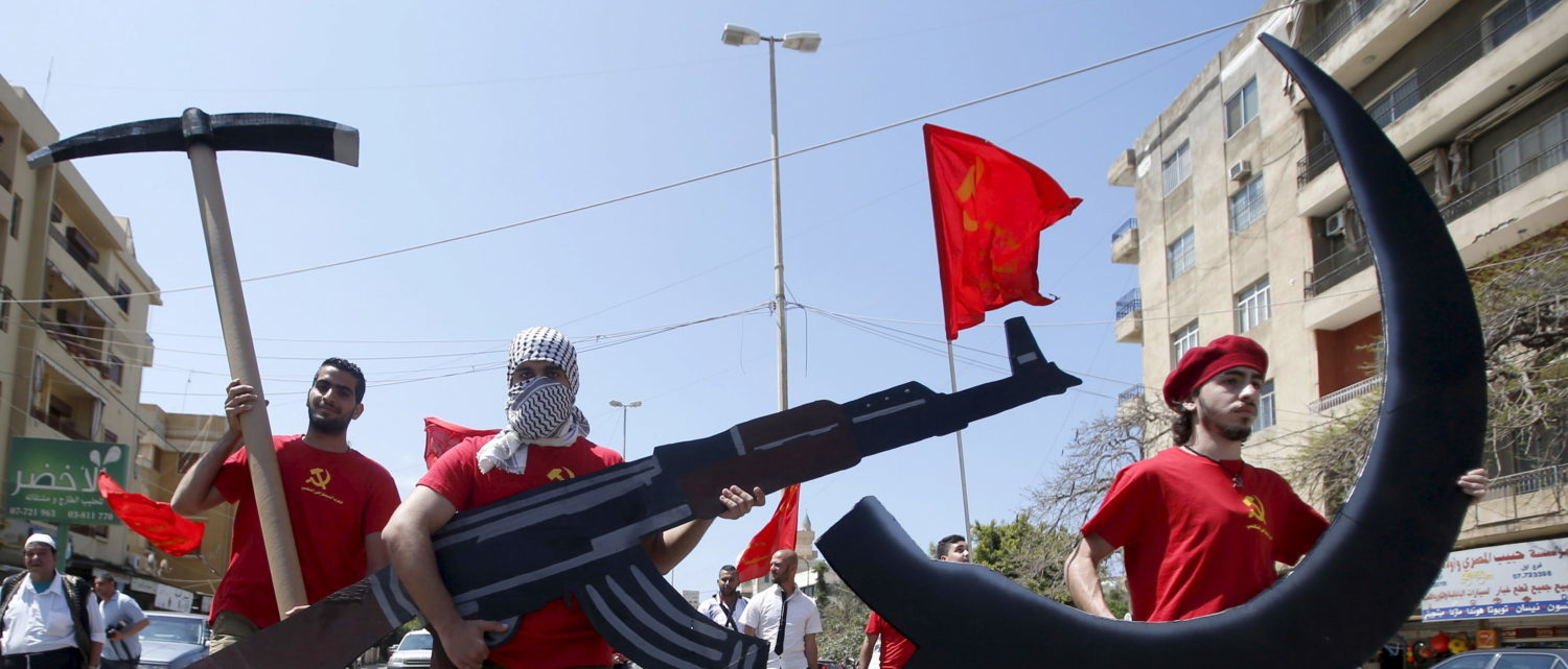 Protestors attend a march organised by the Democratic People's Party members, part of the Lebanese Communist party, carrying a sickle, hammer and Kalashnikov rifle cut outs to mark Labour Day in Sidon, south Lebanon May 3, 2015. International Workers' Day, also known as Labour Day or May Day, commemorates the struggle of workers in industrialised countries in the 19th century for better working conditions. REUTERS/Ali Hashisho - GF10000082588