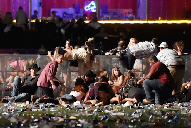 People scramble for shelter at the Route 91 Harvest country music festival after apparent gun fire was heard on October 1, 2017 in Las Vegas. (Photo by David Becker/Getty Images)