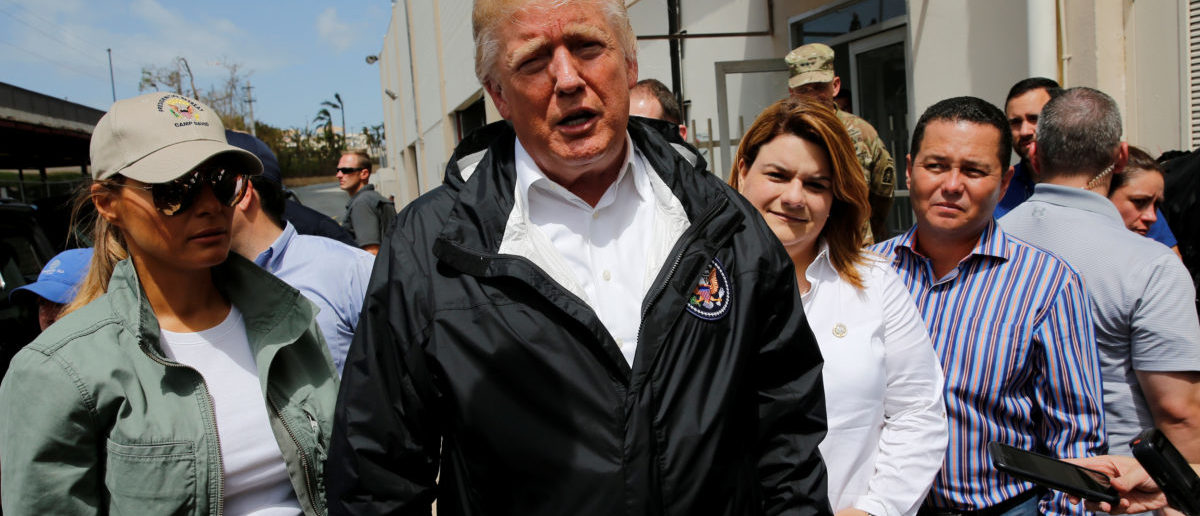 U.S. President Donald Trump, with first lady Melania Trump and local officials, stops to speak with reporters outside a hurricane relief distribution center at Calvary Chapel in San Juan, Puerto Rico, October 3, 2017. REUTERS/Jonathan Ernst