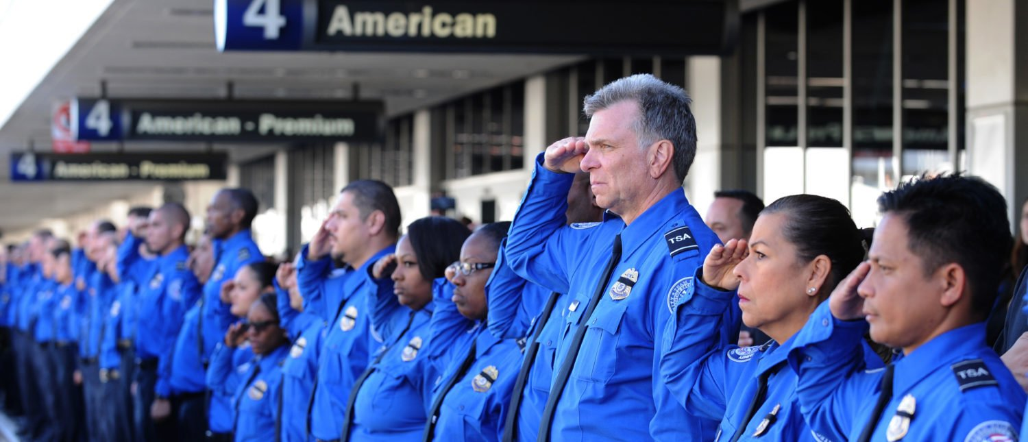 LOS ANGELES, CA - NOVEMBER 6: A long line of TSA personnel salute the U.S. Honor Flag procession as it leaves Los Angeles International Airport in memory of TSA agent Gerardo Hernandez on November 6, 2013 in Los Angeles, California. The Honor Flag will be used at Hernandez's upcoming funeral services. (Photo by Brad Graverson-Pool/Getty Images)
