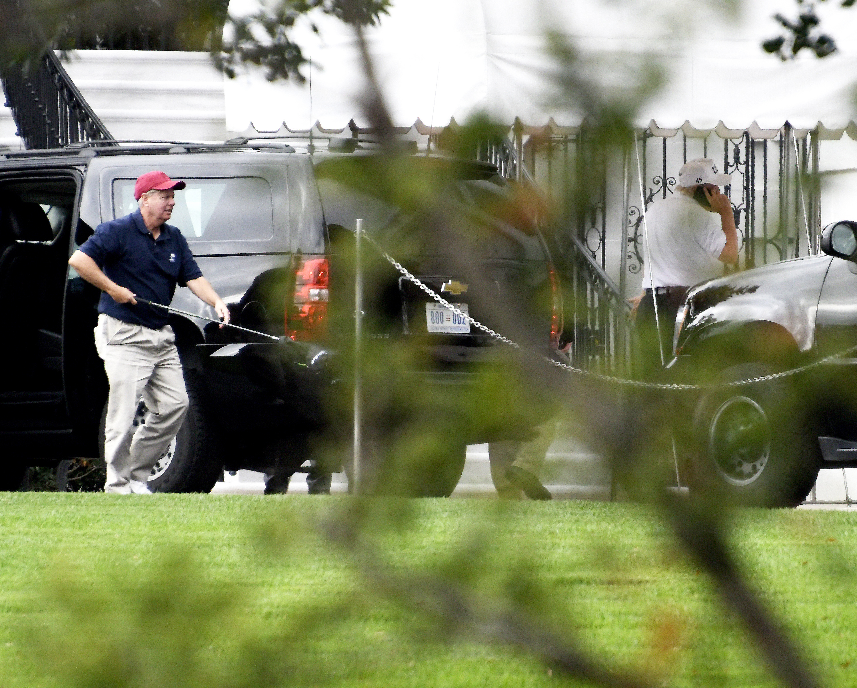 WASHINGTON, DC - OCTOBER 14: (AFP OUT) Senator Lindsey Graham (R-SC), left, carries one of his golf clubs as he leaves the presidential limo at the White House on October 14, 2017 in Washington, DC. U.S. President Donald Trump is seen at right talking on the phone. The two are returning after playing a round of golf. (Photo by Ron Sachs - Pool/Getty Images)