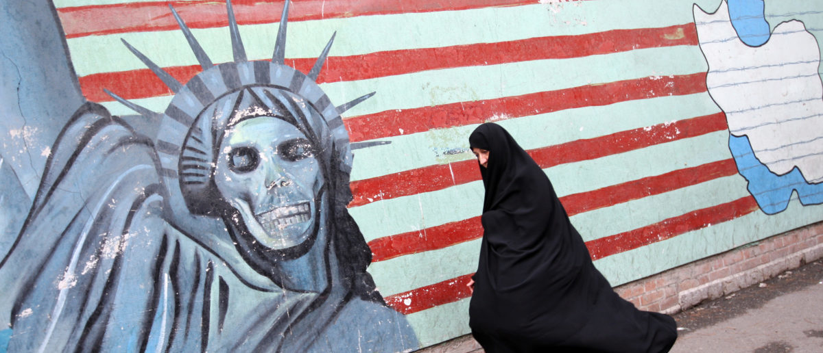 An Iranian woman walks past an anti-US mural painted on the wall of the former US embassy in Tehran on November 4, 2009 to mark the storming of the American embassy by Iranian students 30 years ago. Thousands of Iranians staged the noisy anti-US rally in central Tehran as riot police armed with batons and firing teargas moved in as several hundred opposition supporters attempted to stage an anti-government protest. AFP PHOTO/BEHROUZ MEHRI (Photo credit should read BEHROUZ MEHRI/AFP/Getty Images)