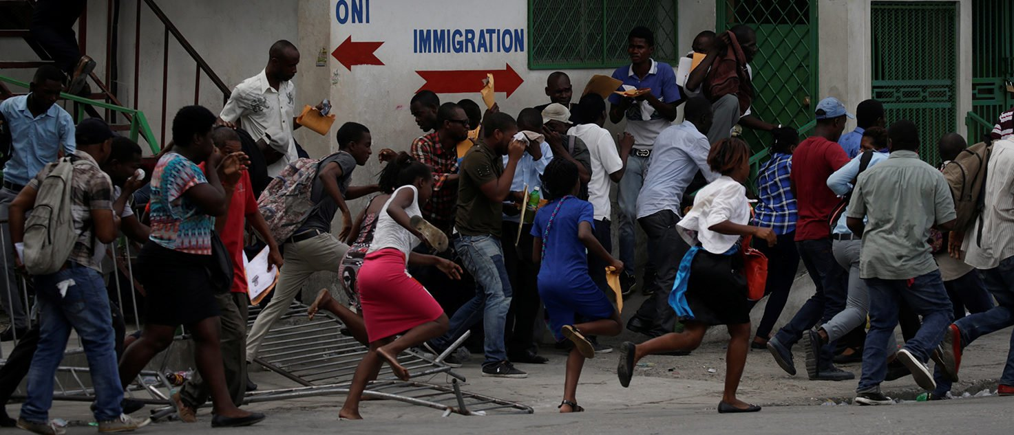 Pedestrians run away after Haitian National Police officers fired tear gas to disperse a demonstration against the government in Port-au-Prince, Haiti, September 28, 2017. REUTERS/Andres Martinez Casares