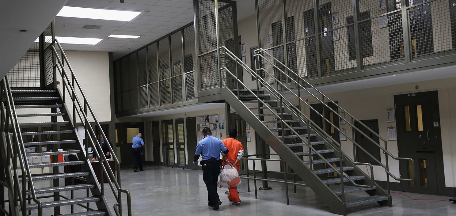 A guard escorts an immigrant detainee from his 'segregation cell' back into the general population at the Adelanto Detention Facility on November 15, 2013 in Adelanto, California. Most detainees in segregation cells are sent there for fighting with other immigrants, according to guards. The facility, the largest and newest Immigration and Customs Enforcement (ICE), detention center in California, houses an average of 1,100 immigrants in custody pending a decision in their immigration cases or awaiting deportation. The average stay for a detainee is 29 days. The facility is managed by the private GEO Group. ICE detains an average of 33,000 undocumented immigrants in more than 400 facilities nationwide. (Photo by John Moore/Getty Images)