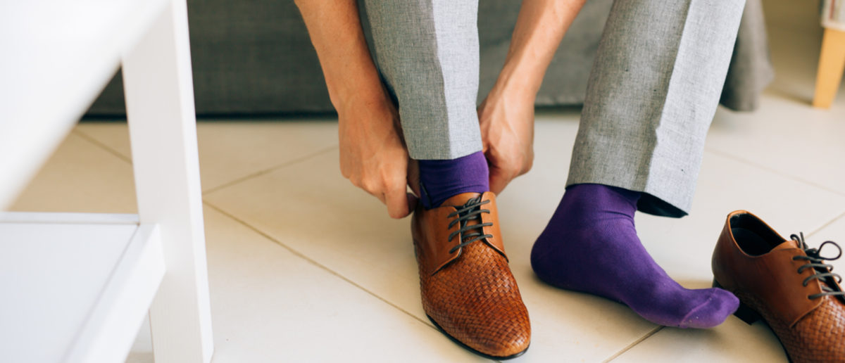 The man in gray slacks and a purple dress socks brown shoes with laces sitting on the couch. nadtochiy (Shutterstock)