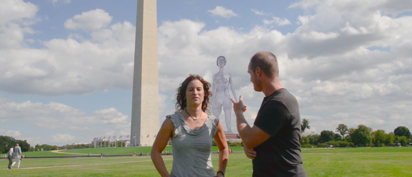 Organizers stand in front of an artist's rendering of the giant naked woman proposed to temporarily stand on the National Mall (Image: Vimeo Screengrab/Catharsis Onthemall)