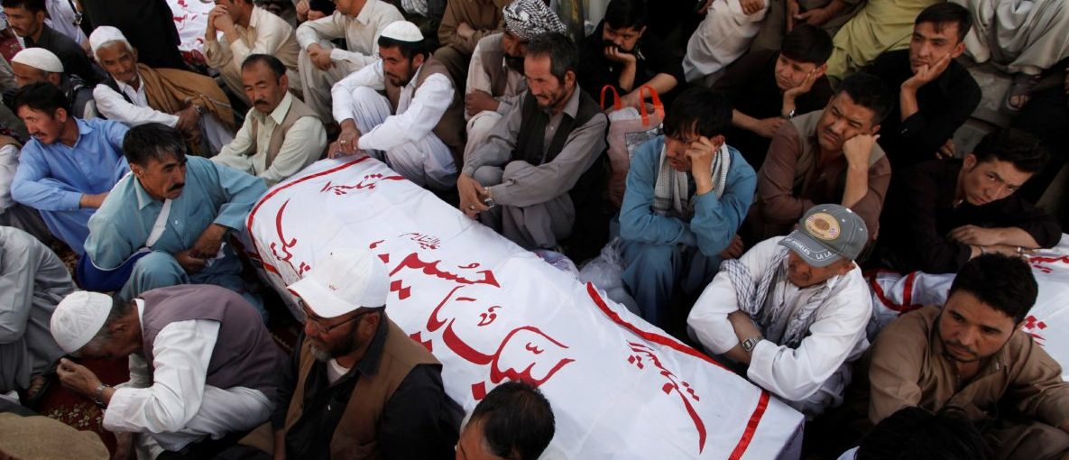 Shi'ite Muslim men from Pakistan's ethnic Hazara minority mourn around the coffins of their relatives, who were killed in a shooting attack, in Quetta, Pakistan October 9, 2017. REUTERS/Naseer Ahmed