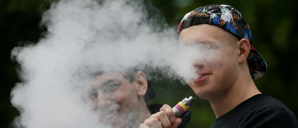 A man exhales electronic cigarette vapour in a park in central Kiev, Ukraine May 12, 2017. REUTERS/Valentyn Ogirenko