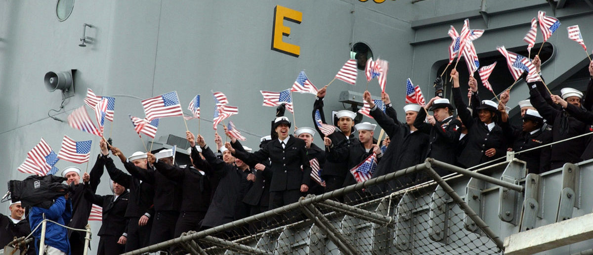 Sailors aboard the USS Roosevelt wave to loved ones as the aircraft carrier returns to port at the U.S. Naval base at Norfolk, Virginia March 27, 2002. [The Roosevelt set a record with 159 consecutive days at sea while supporting Operation Enduring Freedom following the attacks in New York City and Washington D.C.] REUTERS/U.S. Navy/Shane T. McCoy/Handout
