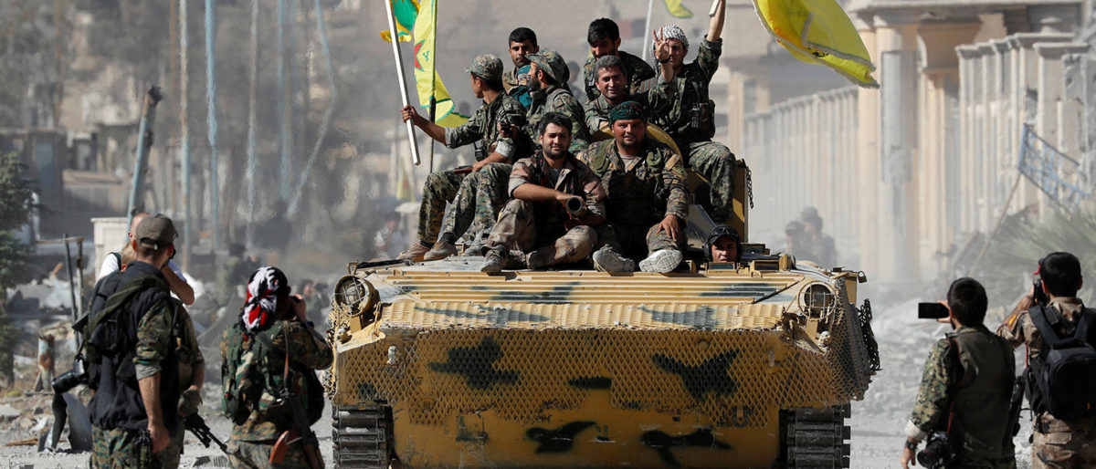 Fighters of Syrian Democratic Forces ride atop of an armoured vehicle after Raqqa was liberated from the Islamic State militants, in Raqqa, Syria October 17, 2017. REUTERS/Erik De Castro