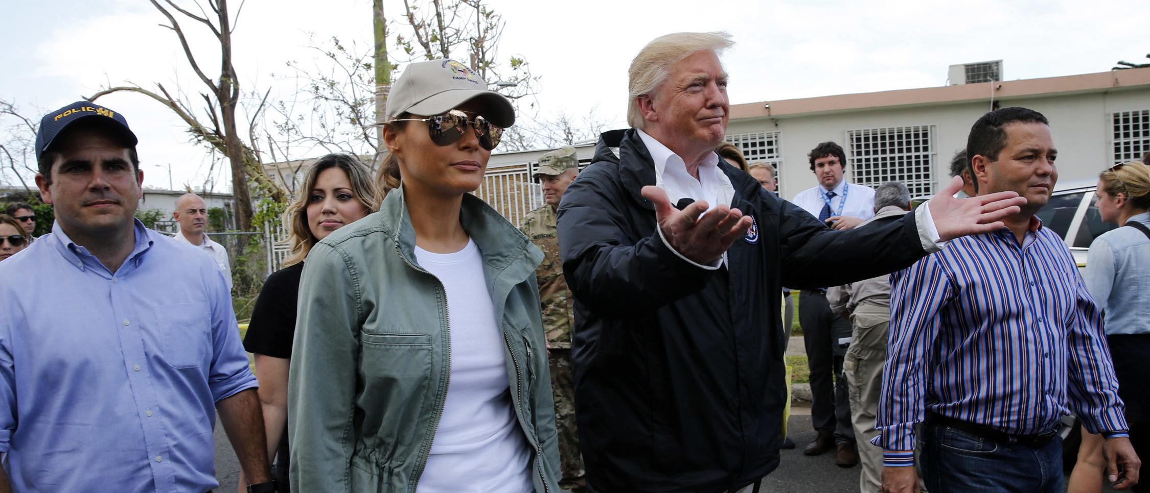 U.S. President Donald Trump and first lady Melania Trump walk through a neighborhood damaged by Hurricane Maria in Guaynabo, Puerto Rico, U.S., October 3, 2017. REUTERS/Jonathan Ernst - HP1EDA31DBA0A
