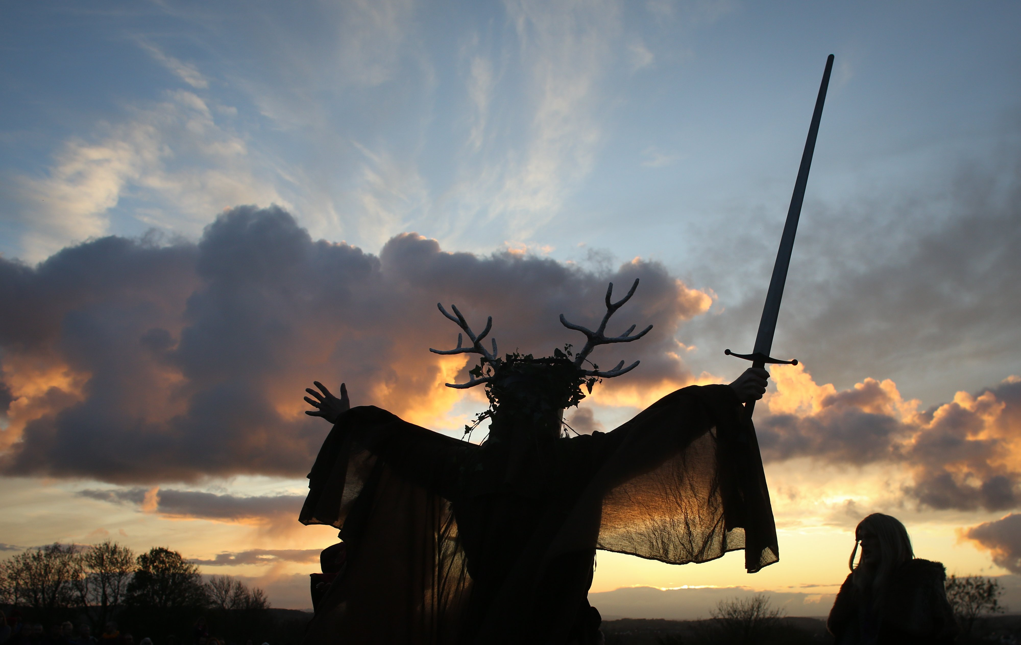 GLASTONBURY, ENGLAND - NOVEMBER 04: A man representing the Winter King holds a sword as he takes part in a sunset ceremony as they celebrate Samhain at the Glastonbury Dragons Samhain Wild Hunt 2017 in Glastonbury on November 4, 2017 in Somerset, England. (Photo by Matt Cardy/Getty Images)