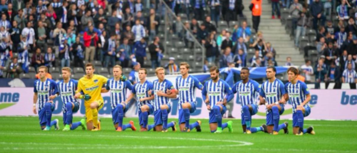 Hertha Berlin players kneel before a game. (Credit: Hertha Berlin/Facebook)