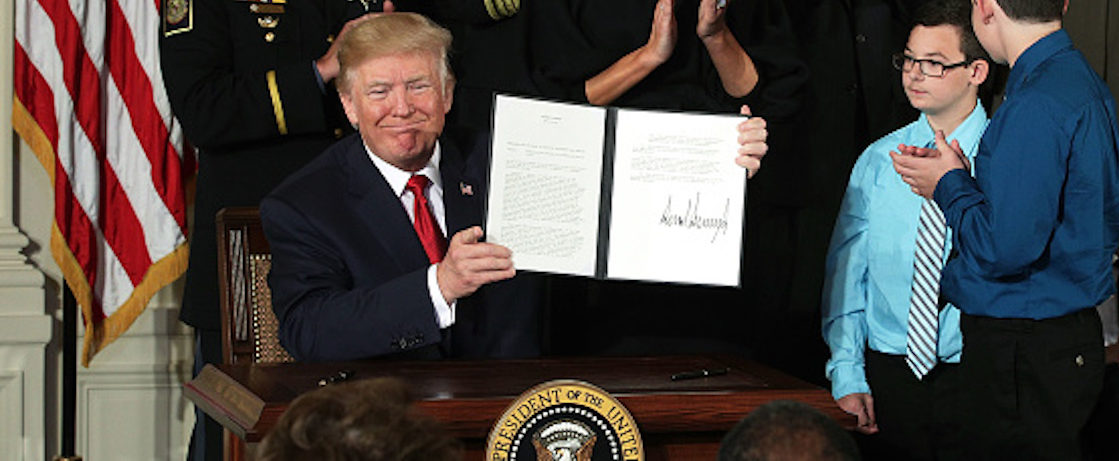 WASHINGTON, DC - OCTOBER 26:  U.S. President Donald Trump shows presidential memorandum that he signed as first lady Melania Trump and other attendees look on during an event highlighting the opioid crisis in the U.S. October 26, 2017 in the East Room of the White House in Washington, DC. Trump plans to authorize the Department of Health and Human Services to declare a nationwide public health emergency in an effort to reduce the number of opioid overdose deaths across the nation.  (Photo by Alex Wong/Getty Images)