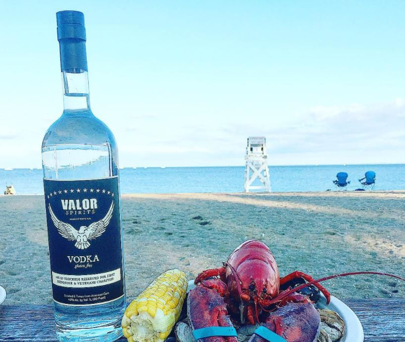 Valor and a lobster hanging out together at the beach. Photo: courtesy of Valor Spirits.
