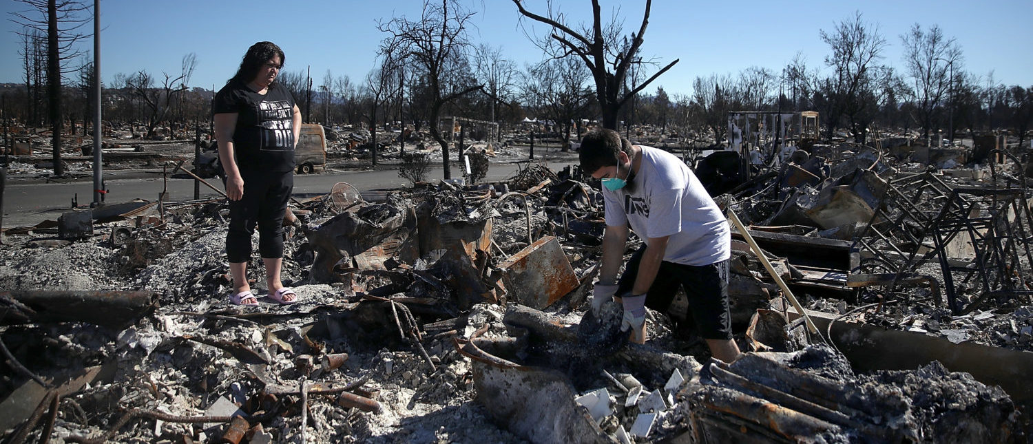 SANTA ROSA, CA - OCTOBER 23:  Renee Hernandez (L) watches her son Ben Hernandez Jr. (R) as he sifts through the remains of their Coffey Park home that was destroyed by the Tubbs Fire on October 23, 2017 in Santa Rosa, California. Residents are returning to their homes after a fast moving and deadly widlfire destroyed 8,400 structures and claimed the lives of at least 42 people.  (Photo by Justin Sullivan/Getty Images)