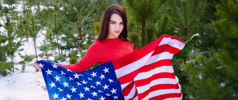 Girl holds American flag (Shutterstock/Oleksandr Masnyi)