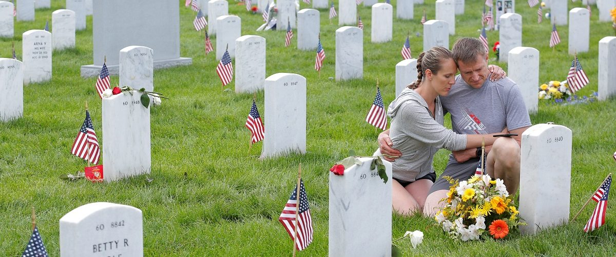 Visitors embrace as they sit next to a grave on Memorial Day at Arlington National Cemetery in Washington