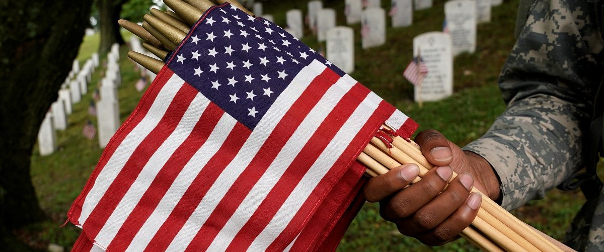 """A soldier from the 3rd U.S. Infantry Regiment (Old Guard) holds a handful of flags during """"Flags-in,"""" where a flag is placed at each of the 284,000 headstones at Arlington National Cemetery ahead of Memorial Day, in Arlington, Virginia, U.S., May 25, 2017. REUTERS/Kevin Lamarque."""
