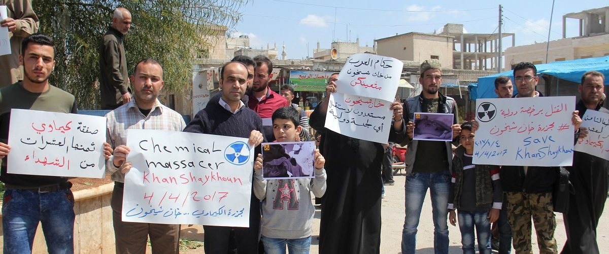 Syrian residents of Khan Sheikhun hold placards and pictures on April 7, 2017 during a protest condemning a suspected chemical weapons attack on their town earlier this week that killed at least 86 people, among them 30 children, and left hundreds suffering symptoms including convulsions, vomiting or foaming at the mouth. (Photo: Omar haj kadour/AFP/Getty Images)