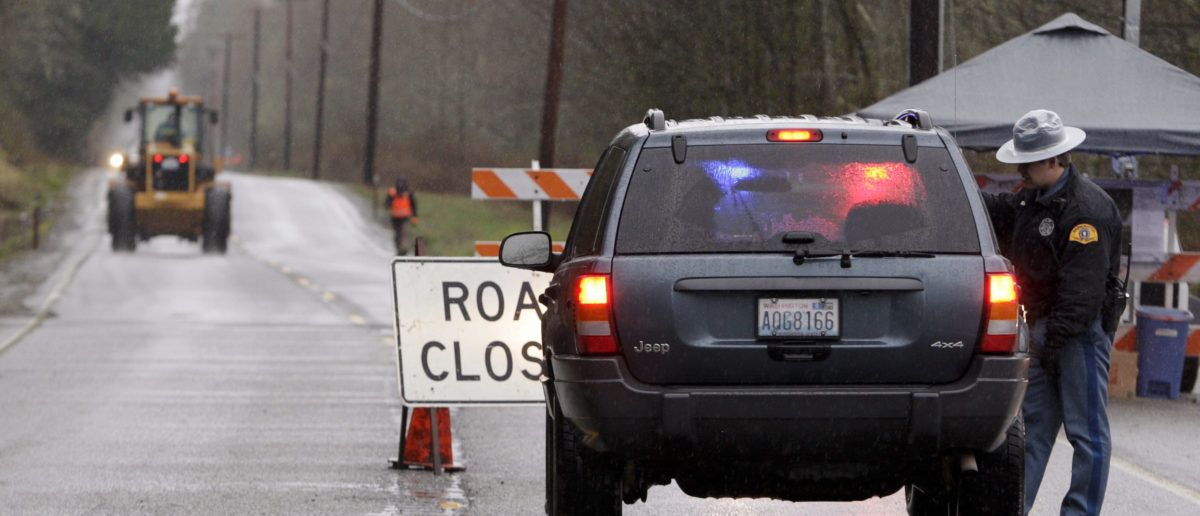 A Washington State Trooper stops a vehicle at a roadblock on Highway 530, near an area where a landslide and floodwaters block the road, outside Darrington, Washington March 28, 2014. At least 26 people were known to have perished when a rain-soaked hillside collapsed without warning on Saturday, unleashing a deluge of mud that flattened dozens of homes in a river valley near the rural town of Oso, in Snohomish County, some 55 miles northeast of Seattle. REUTERS/Jason Redmond